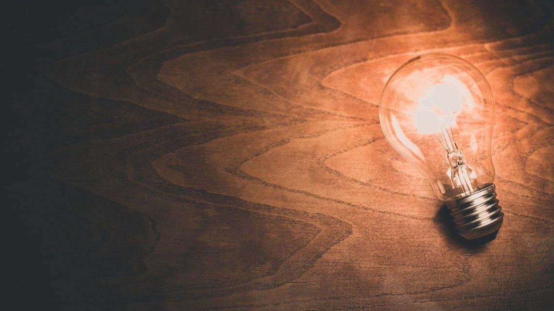 une ampoule allumée sur une table en bois projette sa lumière