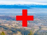 """paysage du pays de gex sur lequel on voit le symbole """"+"""" rouge de l'Hopital rouge"""