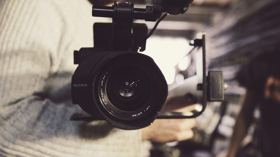 une personne tient une grande caméra professionnelle